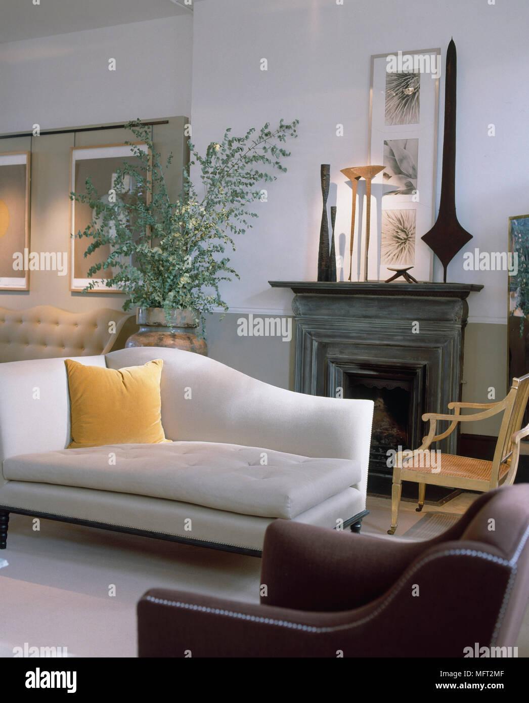 Salon avec murs blancs et verts les illustrations encadrées cheminée avec sculpture crème