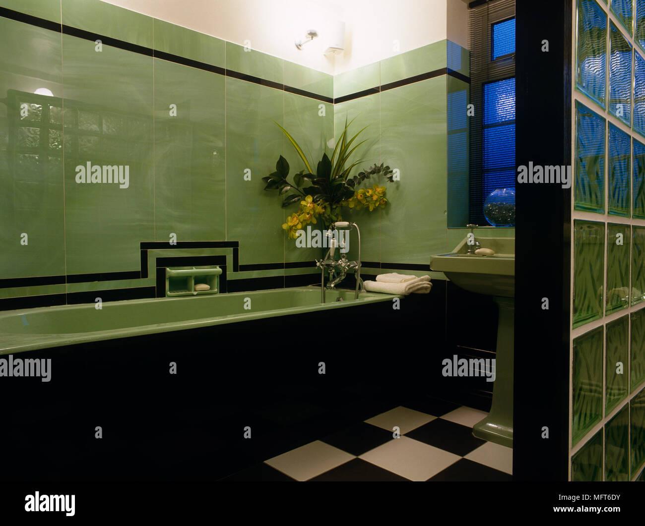 Baignoire dans la salle de bains avec carrelage vert de ...