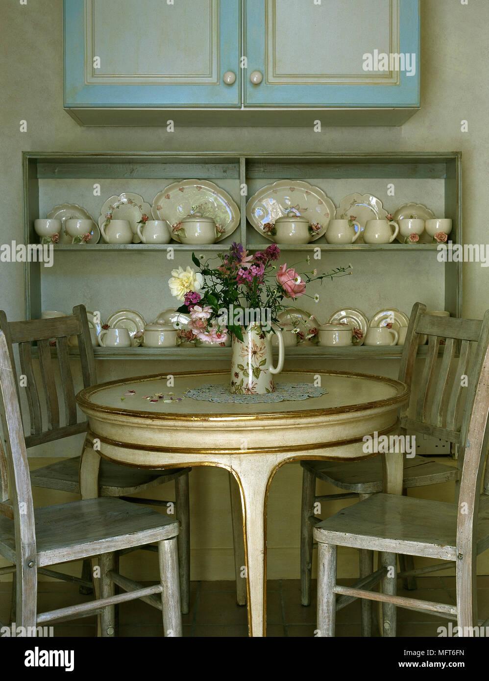 Incroyable Salle à Manger Traditionnelle Avec Table Ronde En Bois Doré, En Détresse,  Des Chaises Et Une Chine Collection Affichée Sur Des Rayonnages Ouverts.