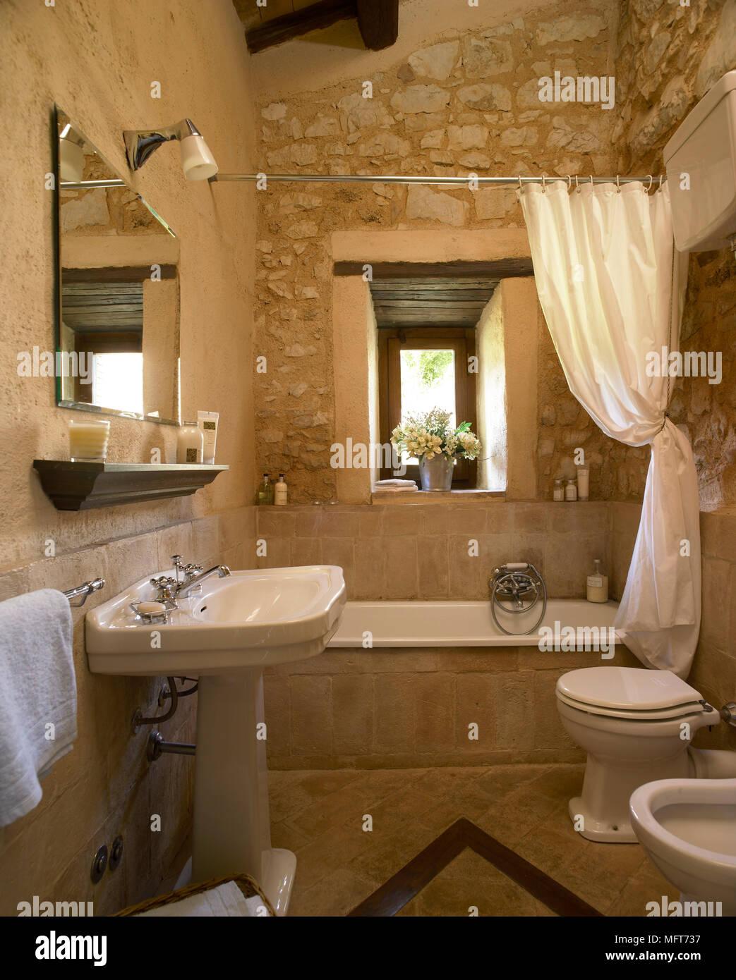 Une salle de bain pays avec des murs en pierre rustiques, baignoire ...
