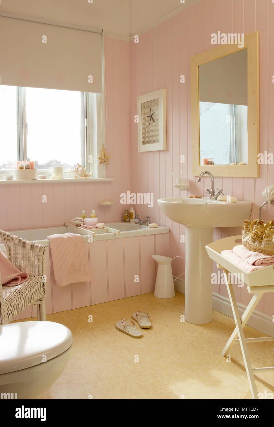Lavabo sur colonne à côté de baignoire dans salle de bains rose ...