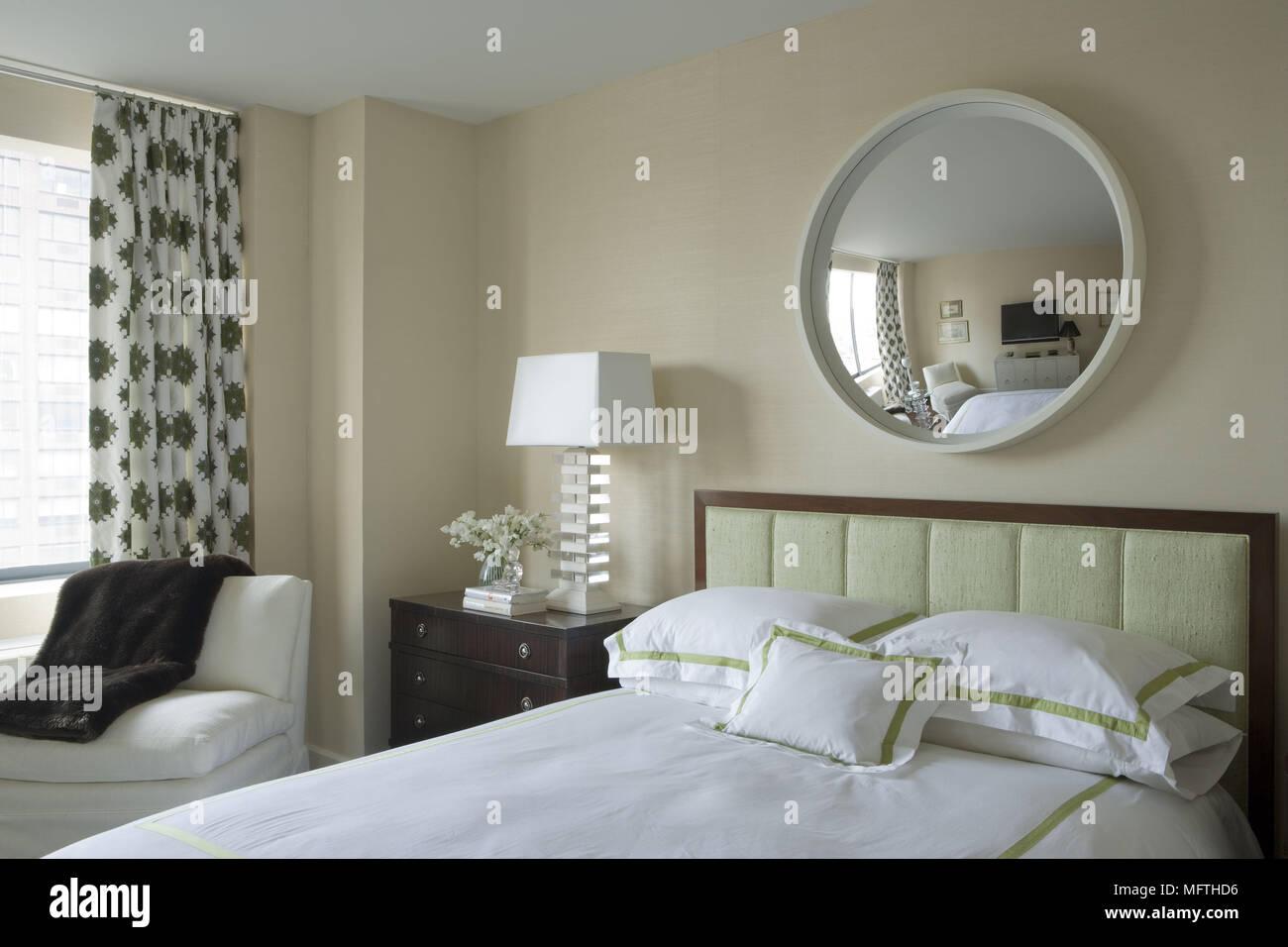 Miroir rond au-dessus de lit double dans la chambre à ...