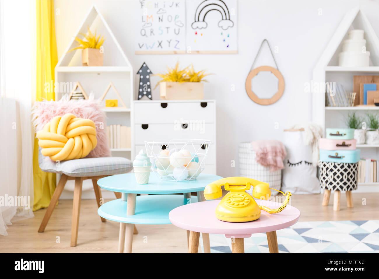 Téléphone jaune placé sur tabouret rose pastel dans des chambre d ...