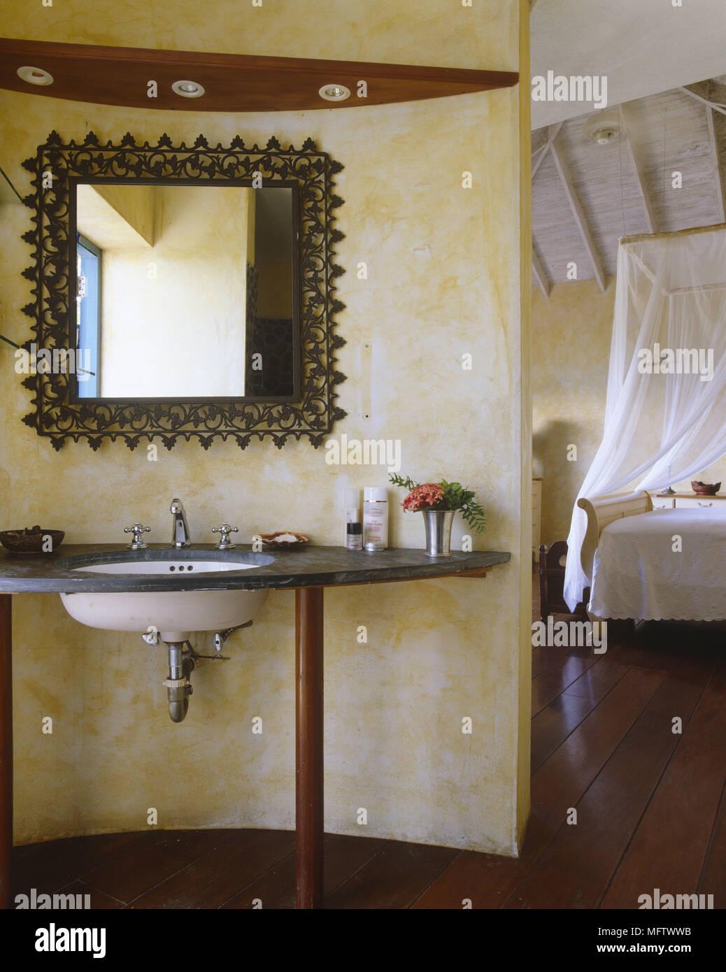 Salle de bain avec lavabo et miroir menant à une chambre ...