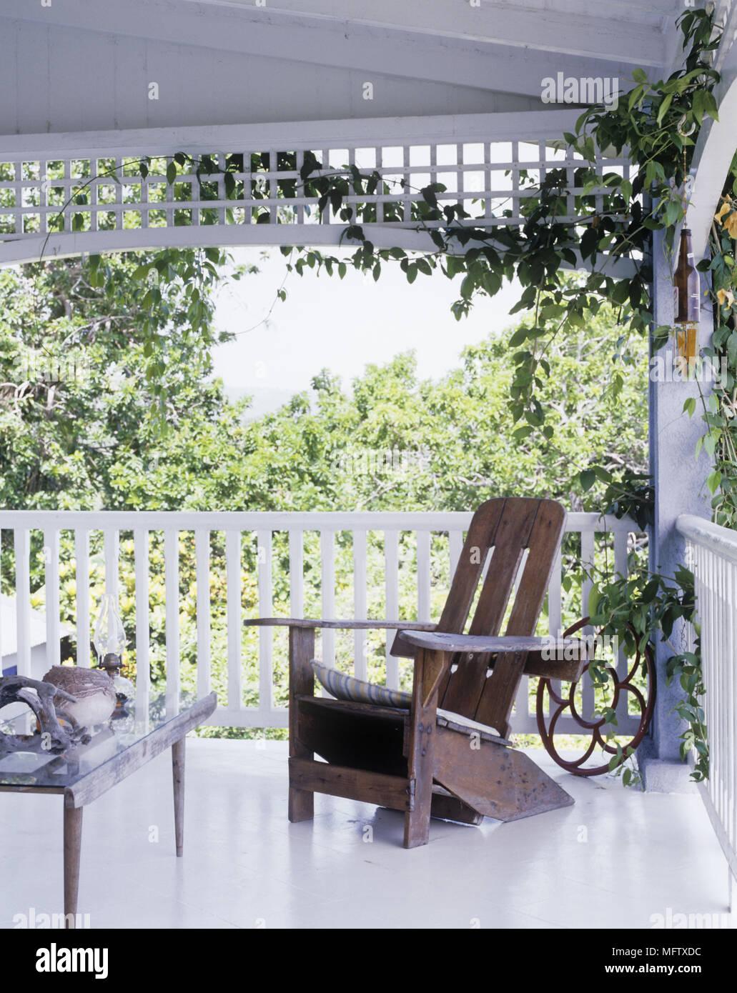 Véranda en bois blanc avec table et chaise en bois donnant ...