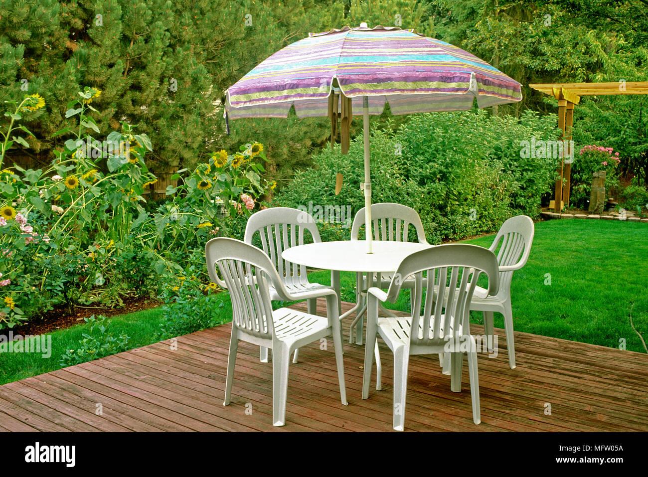 Tables et chaises en plastique avec un parasol sur la ...