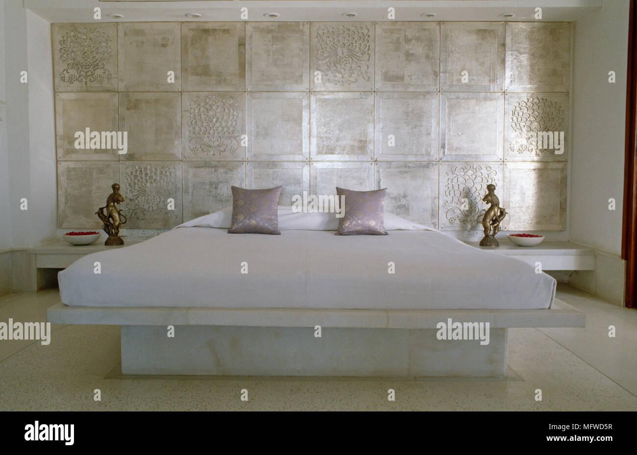 Lit King size avec plate-forme de marbre contre mur carrelé dans ...