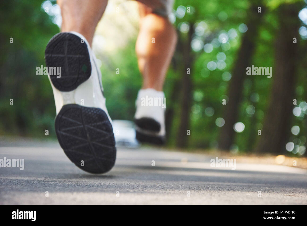 Piscine de la course cross-country dans le concept de l'exercice, de fitness et de mode de vie sain. Close up de pieds de jeune homme qui court le long du canal dans le parc de la route Photo Stock
