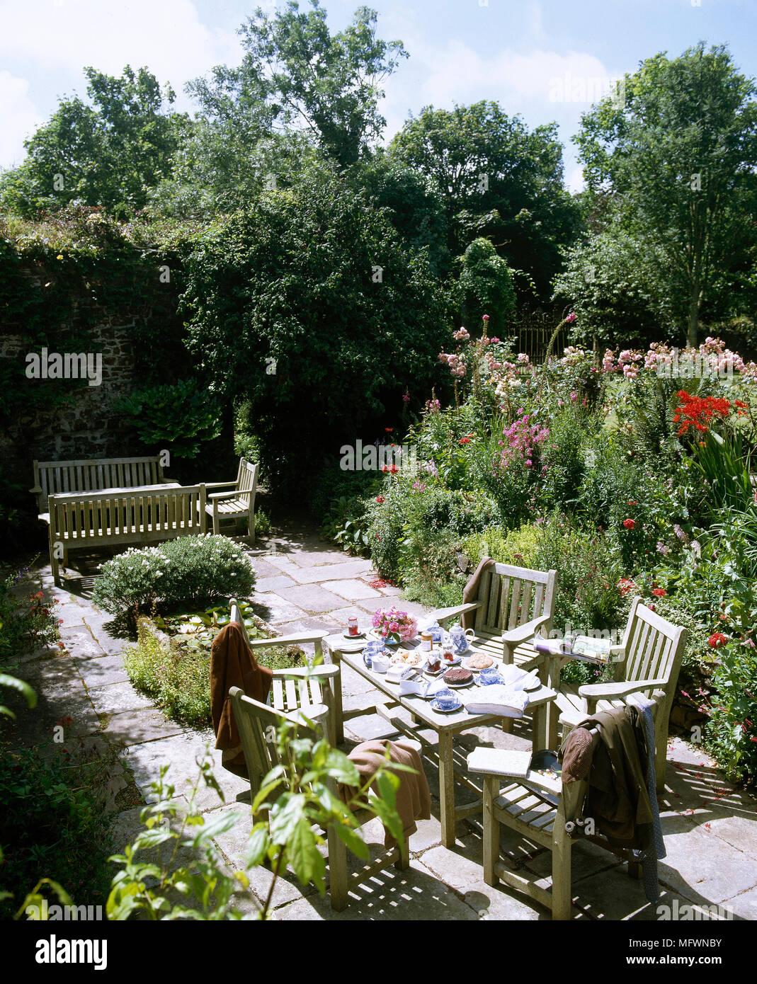 Patio arrière en bois avec une table de jardin et chaises ...