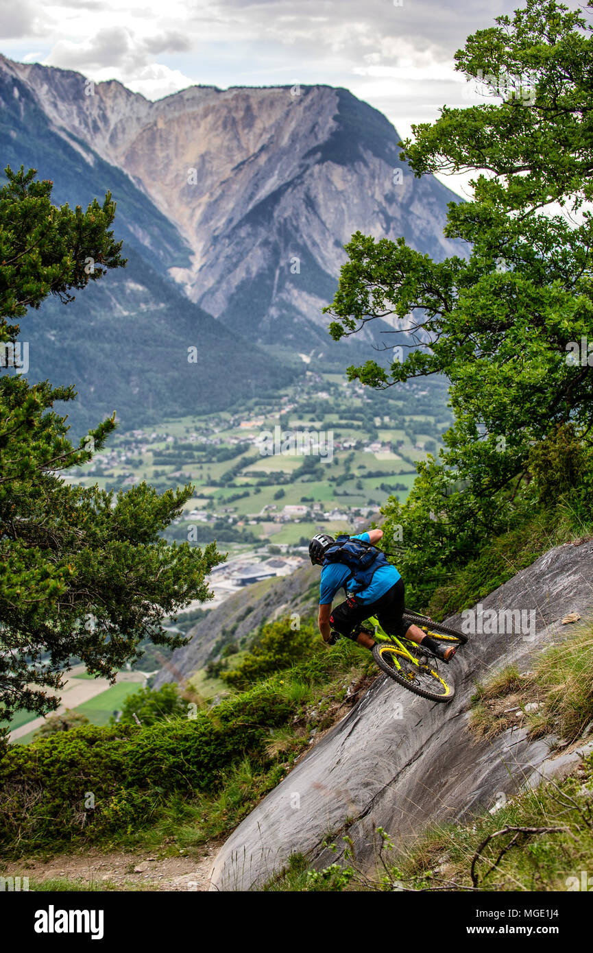 Un homme monte un vtt haut au-dessus de la vallée, près des villes de Gampel et Jeizinen dans le Valais Suisse. Banque D'Images