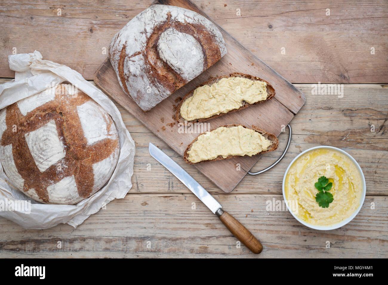 Pain de levain et pain de levain d'épeautre avec houmous faits maison sur une planche à pain. ROYAUME-UNI. Banque D'Images