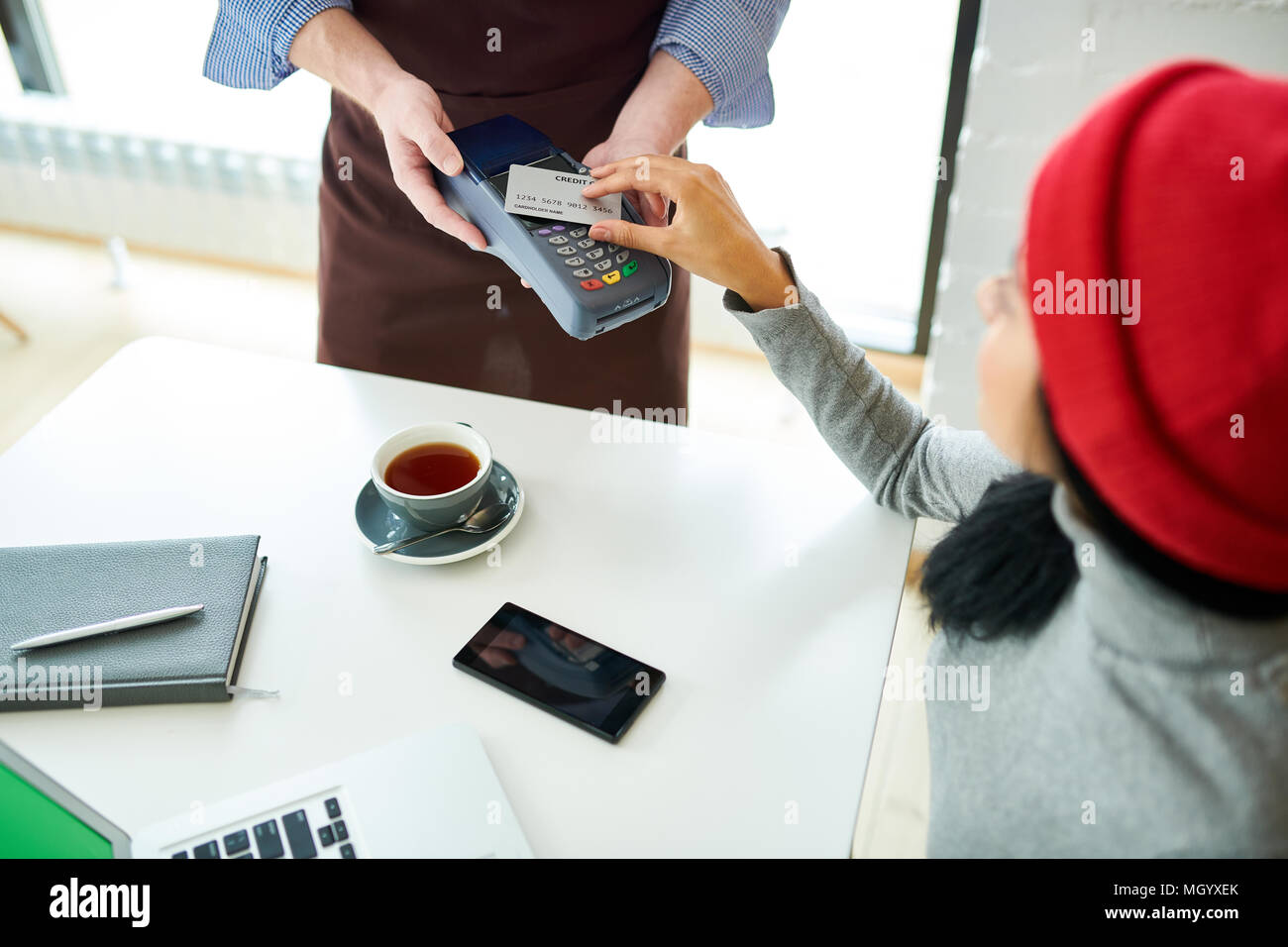 Jeune femme de payer via NFC in Cafe Photo Stock
