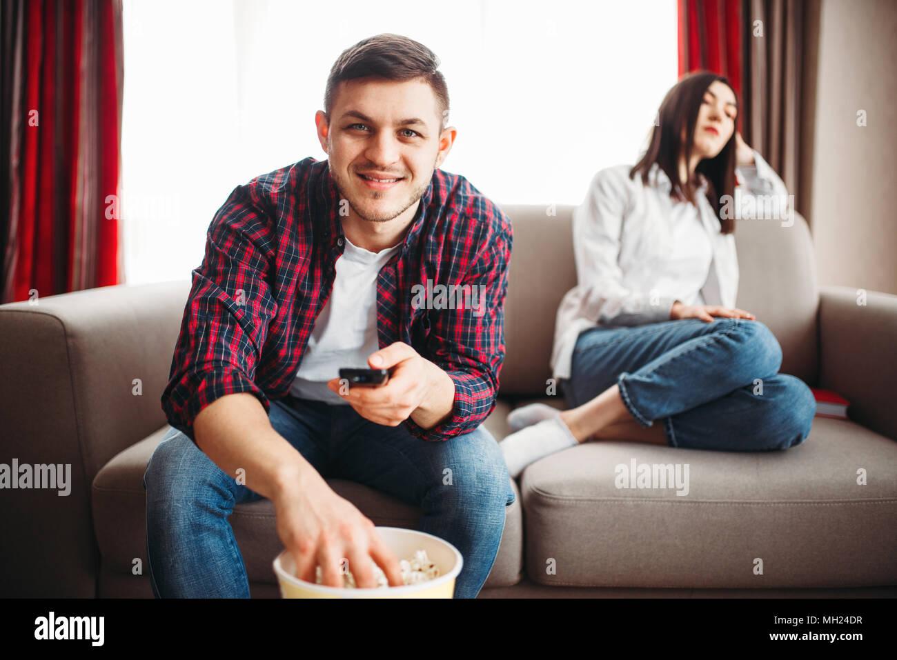 Regarder la télévision et de l'homme mange du pop-corn, femme de mauvaise humeur Photo Stock