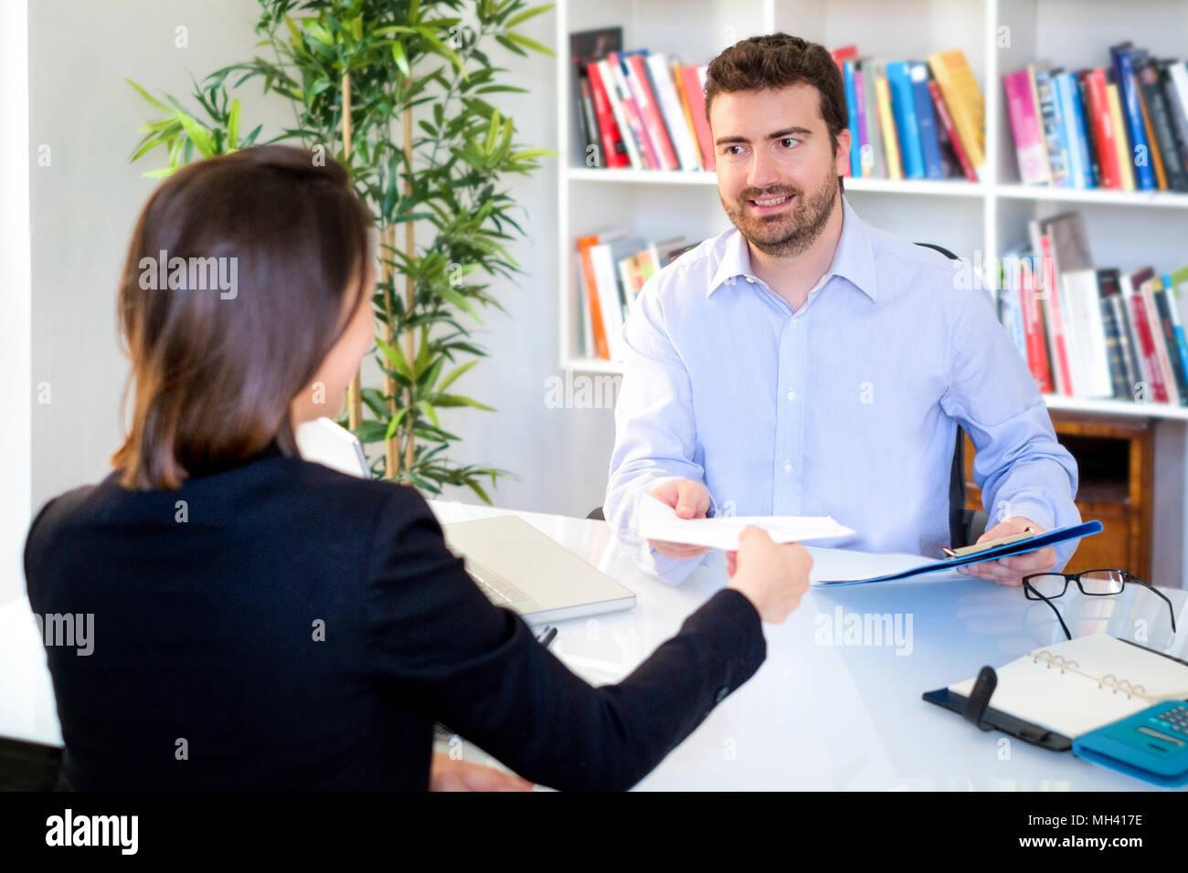 Jeune candidat montrant son curriculum annonce lors d'entretien d'embauche Photo Stock