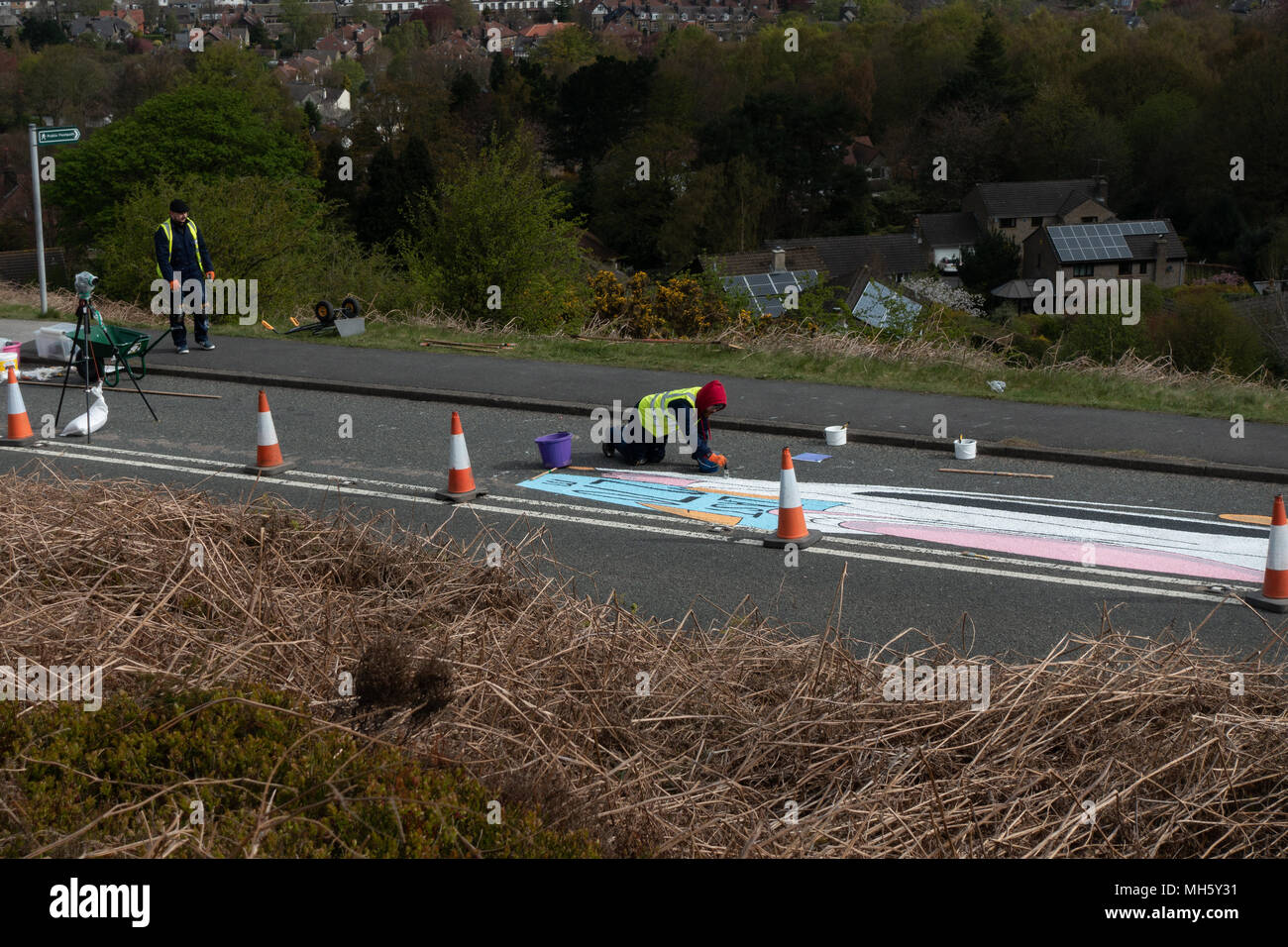 Ilkley Moor, West Yorkshire, Royaume-Uni. 30 avril 2018. Artistes, passer des heures sur leurs genoux, peindre le Tour de Yorkshire's premier sommet terminer sur la Vache et son veau road prêt pour la course de vendredi. Qu'est-ce que cela va être? Land art (anamorphique) Rebecca Cole/Alamy Live News Photo Stock
