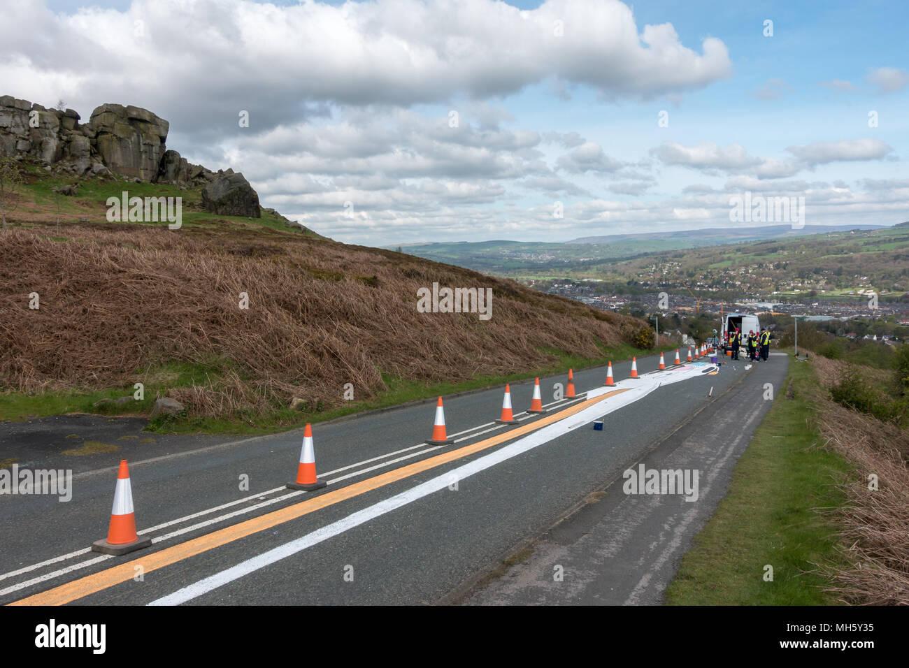 Ilkley Moor, West Yorkshire, Royaume-Uni. 30 avril 2018. Repos artistes genoux après avoir passé des heures à peindre le Tour de Yorkshire's premier sommet terminer sur la Vache et son veau road prêt pour la course de vendredi. Qu'est-ce que cela va être? Land art (anamorphique) Rebecca Cole/Alamy Live News Photo Stock