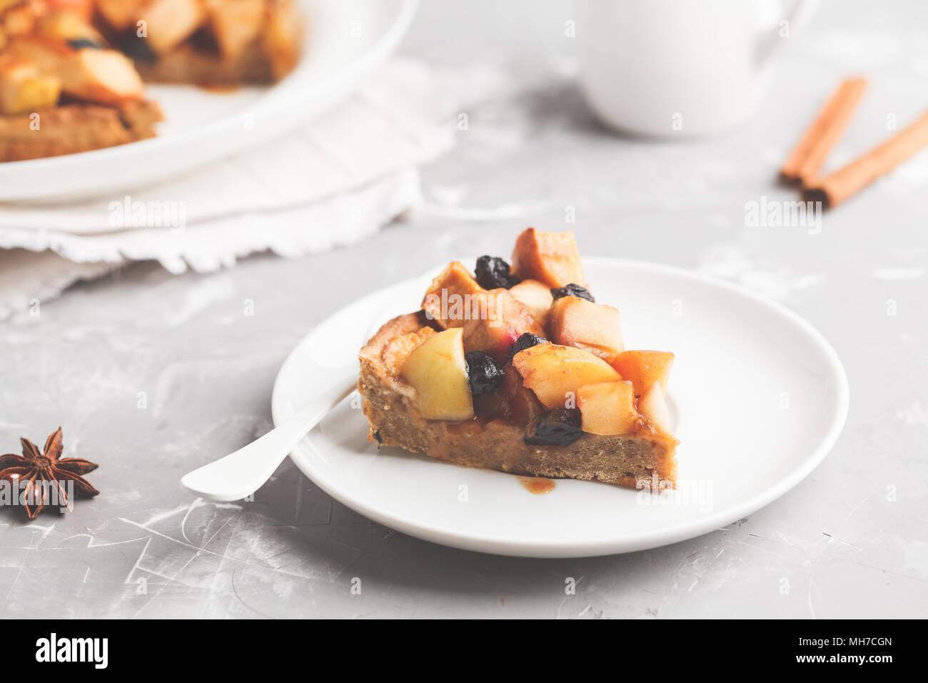 Morceau de vegan tarte aux raisins et cannelle, caramel, fond gris. Photo Stock