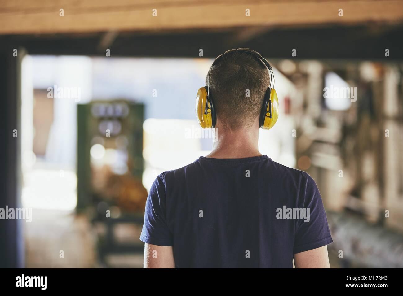 Homme travaillant dans une scierie. Vue arrière du travailleur avec casque. Photo Stock