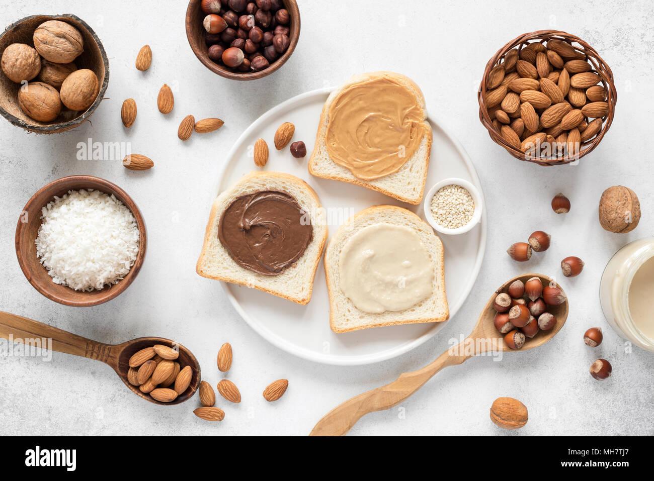 Beurre de noix et de pain grillé sur plaque blanche. Assortiment de beurre de noix tartiner sur du pain blanc grillé. La saine alimentation, végétalien, végétarien, mode de vie sain, de la nutr Photo Stock