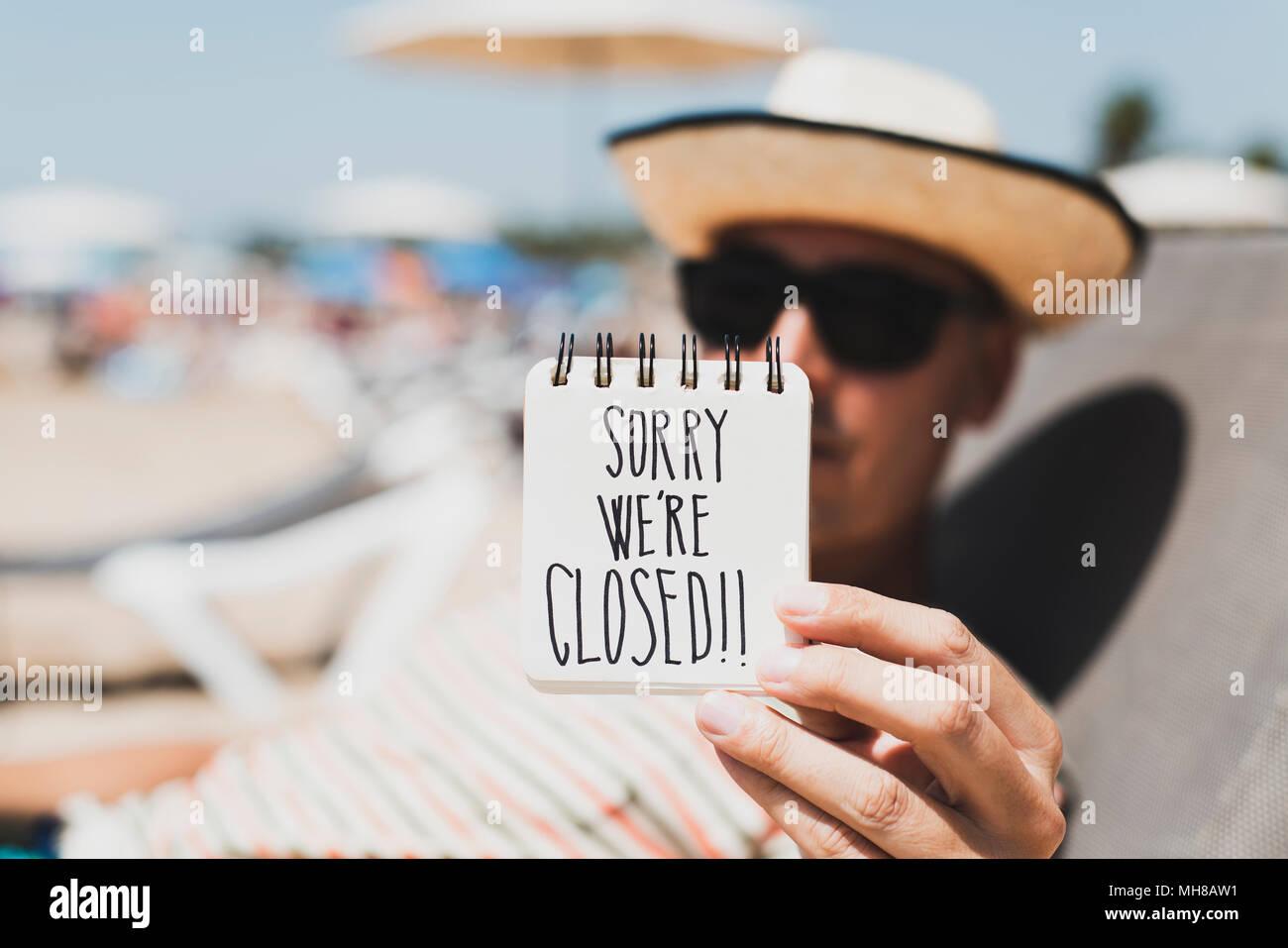 Libre d'un jeune homme portant des lunettes de soleil et chapeau de paille se détendre dans une chaise longue à la plage montrant une spirale bloc-notes avec le texte désolé nous sommes clos Photo Stock