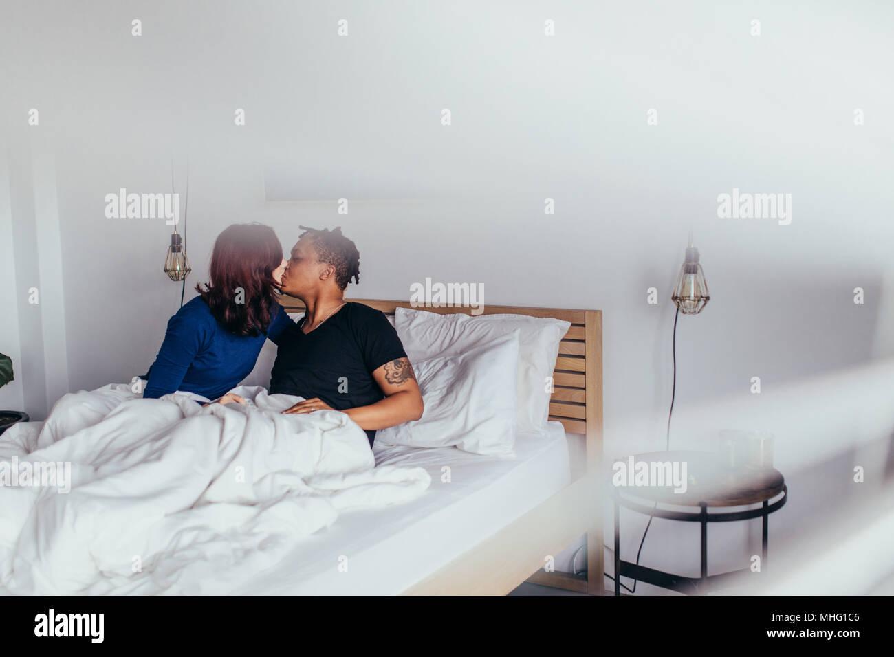 Couple romantique au lit. L'Interracial l'homme et la femme assis sur le lit et s'embrassent. Banque D'Images
