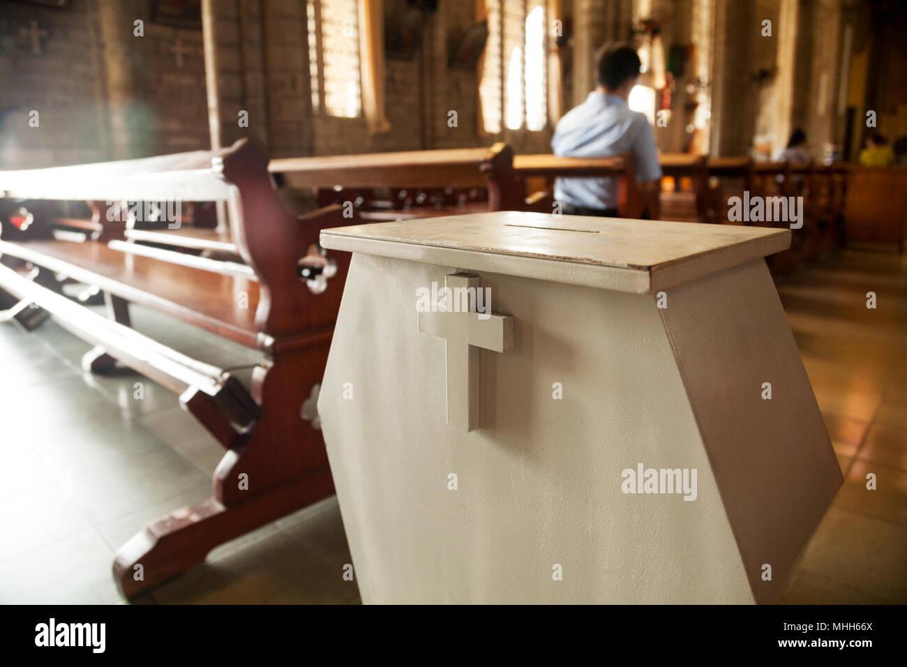 Donation box blanc avec une croix sur elle à une église chrétienne. Boîte de collecte de l'offertoire généreux au milieu de bancs à un temple Catholique Photo Stock