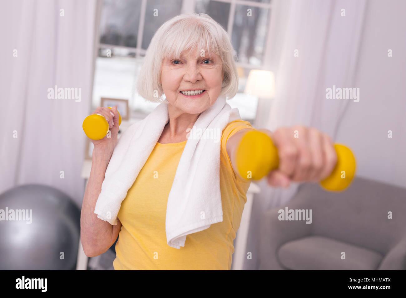 Vieille femme joyeuse l'entraînement avec haltères courtes Photo Stock