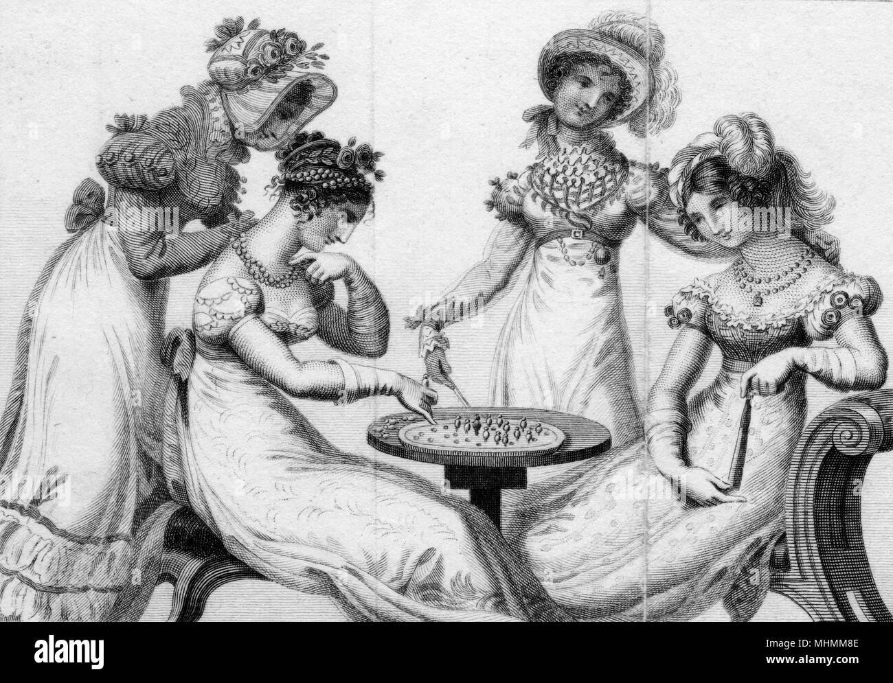 Quatre femmes à la mode de jouer au solitaire. Date: début du 19ème siècle Photo Stock
