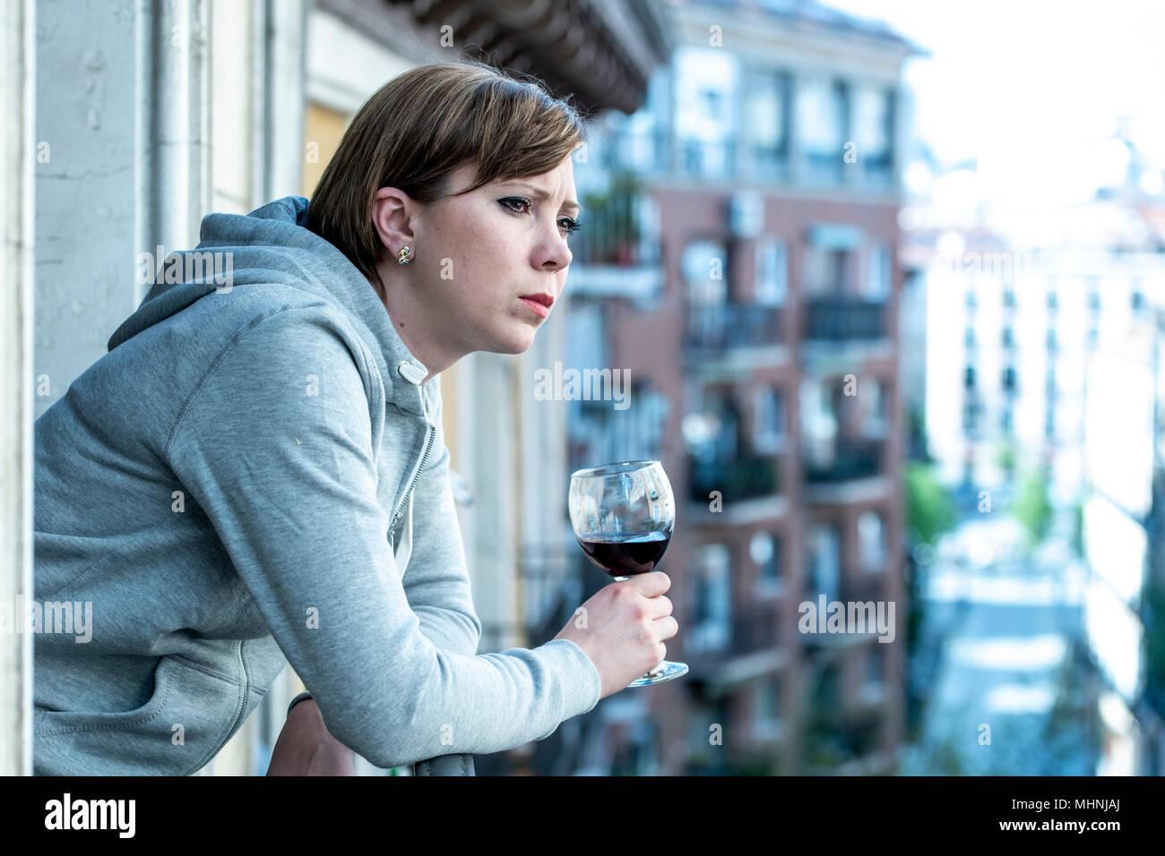 Belle red haired woman souffrant de dépression tenant un verre de vin sur un balcon à la maison. Staring out sentiment de tristesse, de douleur et de chagrin. Photo Stock