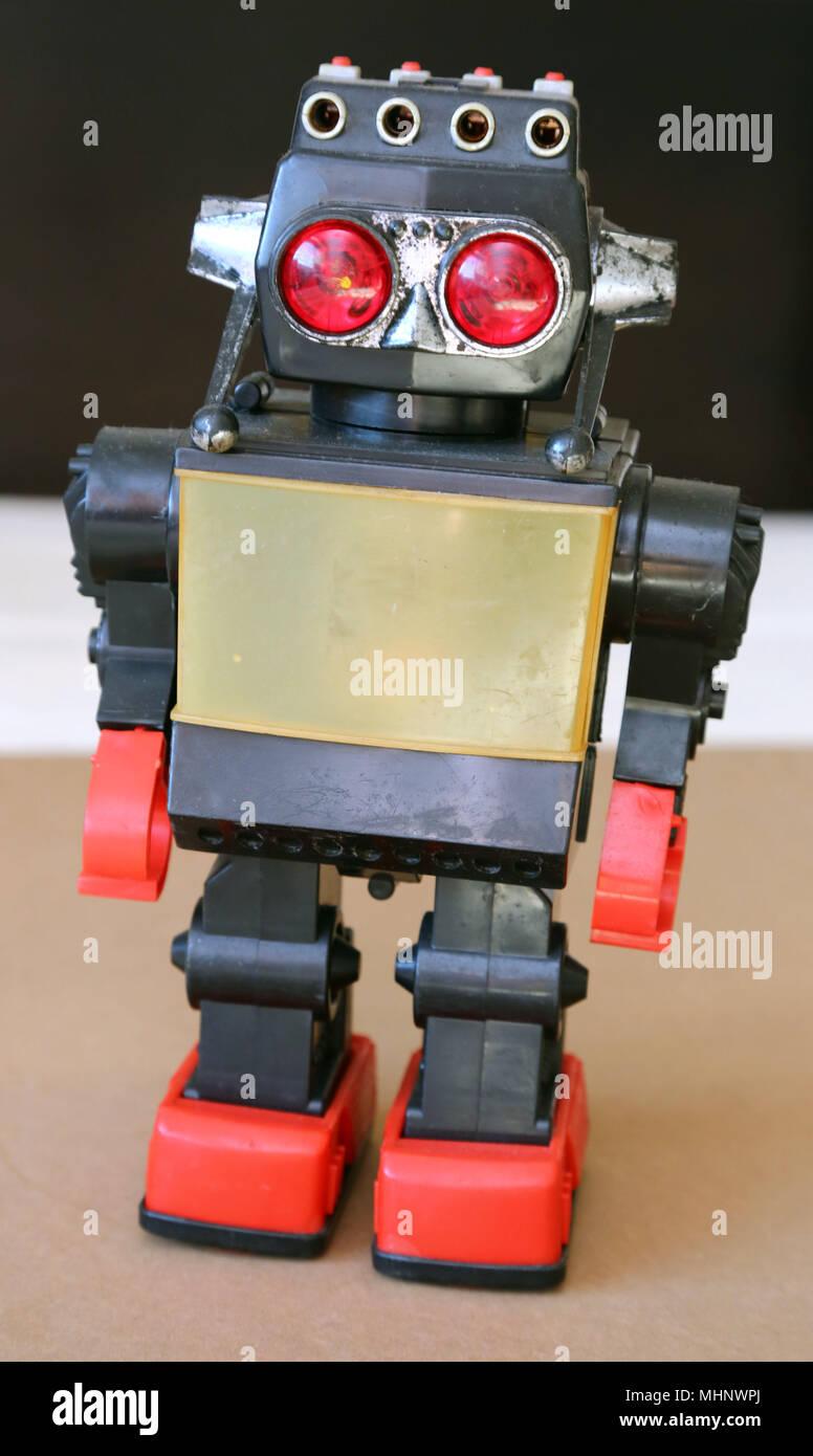 Retro Toy robot en plastique marche avec corps gris, gros yeux rouges et pieds rouges. Photo Stock