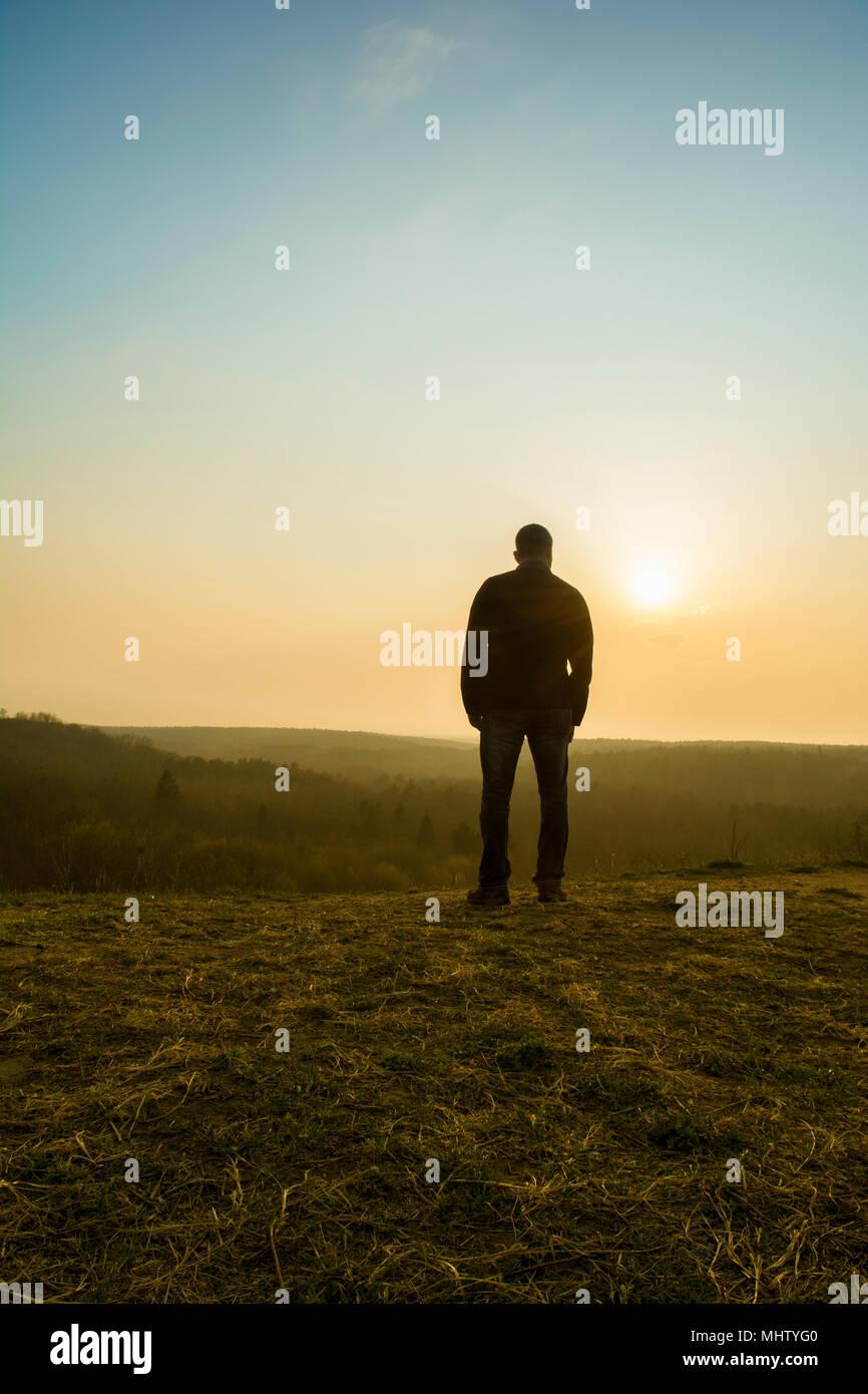 Vue arrière d'un homme regardant le coucher de soleil depuis le sommet d'une montagne Photo Stock