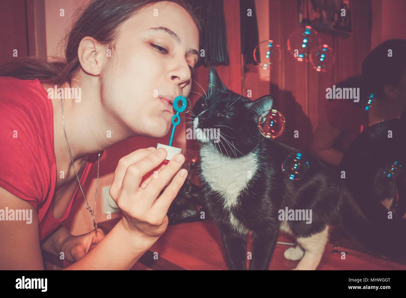 Close-up girl soufflant des bulles de savon et curieux chat noir et blanc qui s'intéressent à eux. Photo Stock