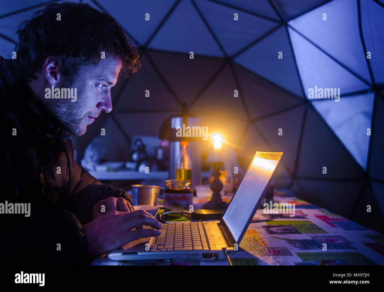 L'homme sur l'expédition, using laptop in camp, camp, Fletanes Narsaq, Kitaa, Groenland Photo Stock