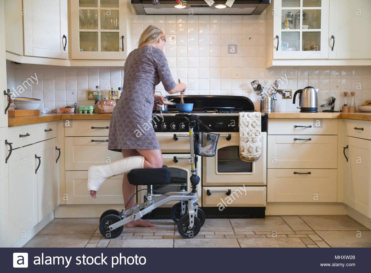 Femme avec la jambe en plâtre à l'aide d'aide à la mobilité tout en repas de cuisine Photo Stock