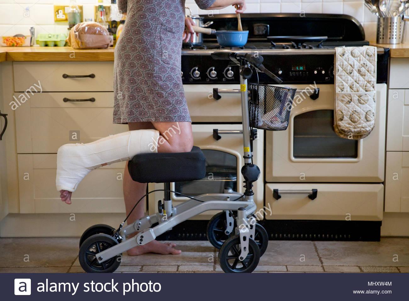 Close Up of Woman avec patte en plâtre à la maison à l'aide d'aide à la mobilité tout en repas de cuisine Photo Stock