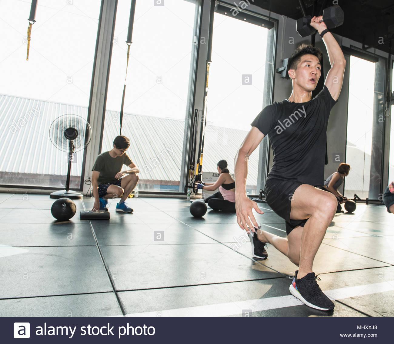 Groupe de personnes travaillant dans une salle de sport, l'homme en premier plan poids de main levée Photo Stock