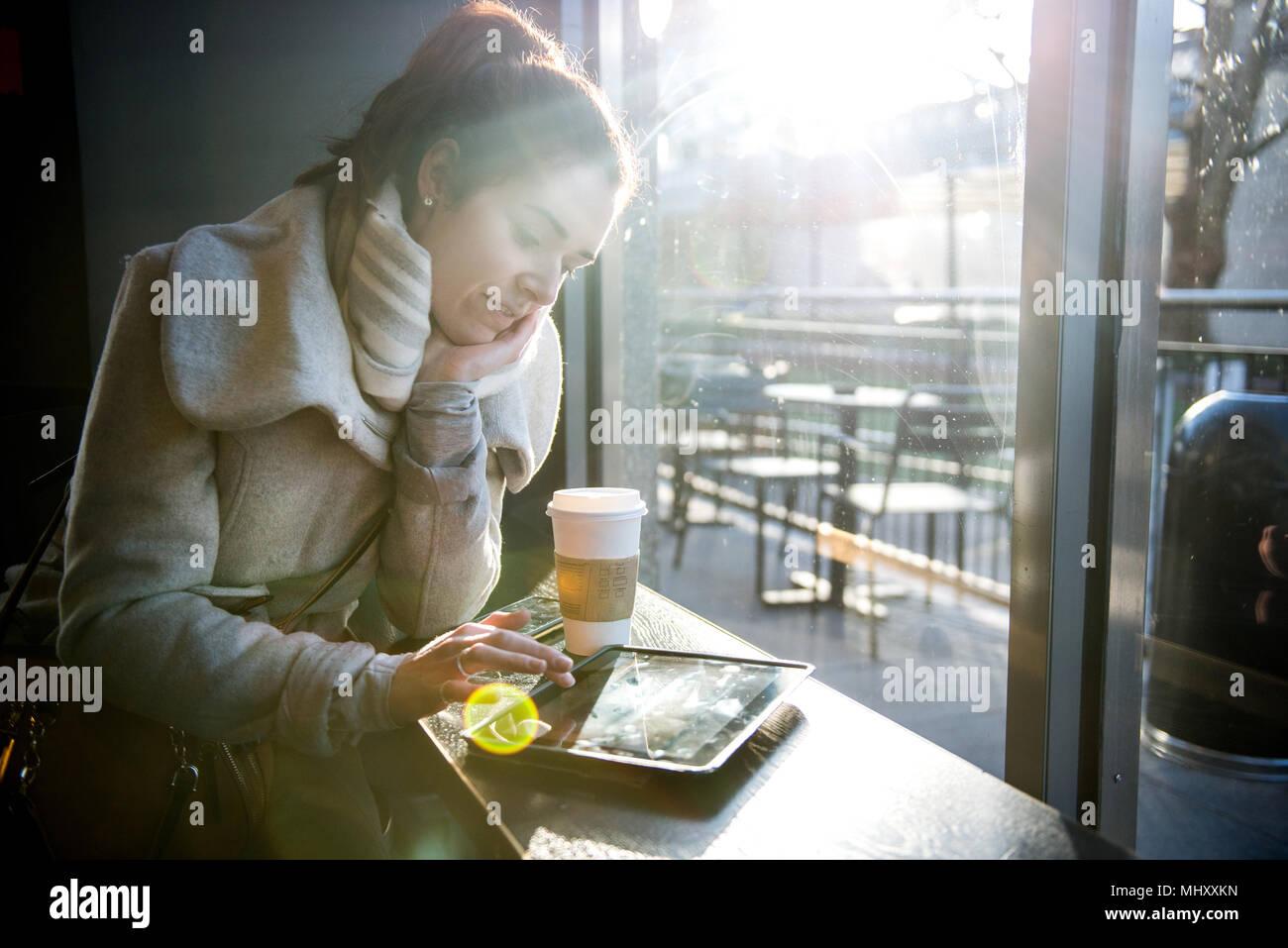 Jeune fille assise dans un café, à l'aide de tablette numérique, London, England, UK Photo Stock
