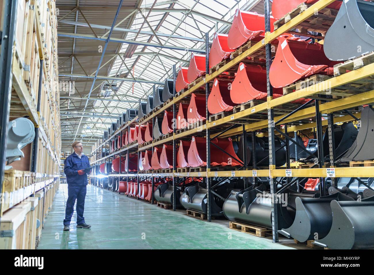 Travailleur dans l'espace de stockage dans l'usine d'ingénierie Photo Stock