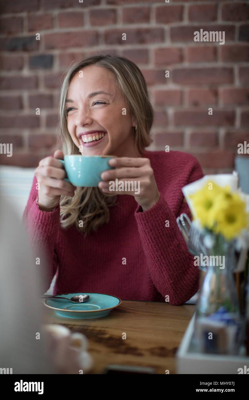 Woman sitting in cafe, boire du café, smiling Photo Stock