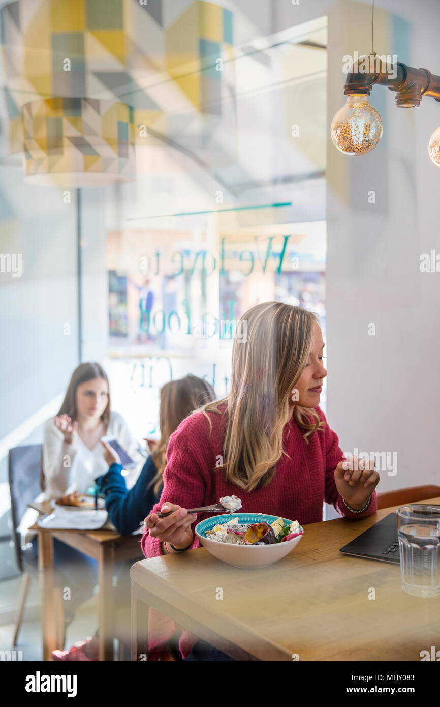 Woman eating muesli dans cafe, using laptop Photo Stock