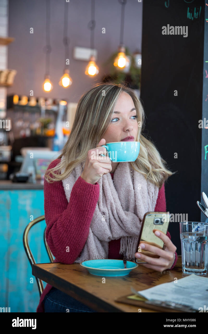 Woman sitting in cafe, holding smartphone, boire du café Photo Stock