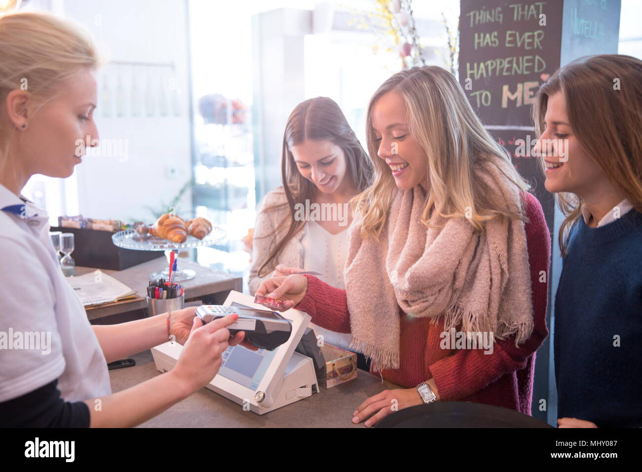 Female friends standing at counter in cafe, le paiement par carte de crédit Photo Stock