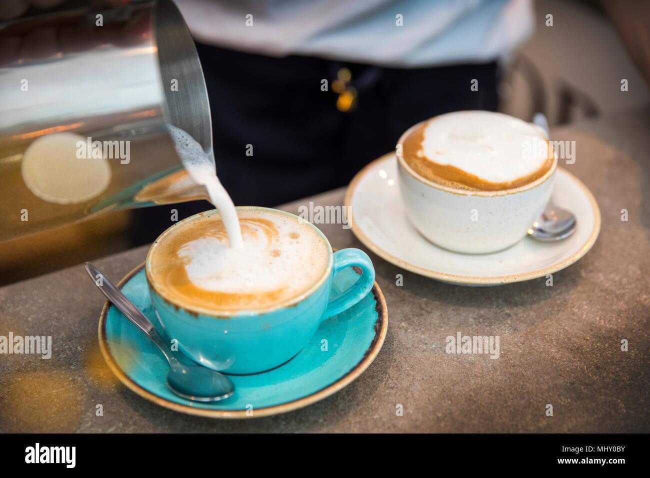 Barista pouring du lait moussé en tasse à café, close-up Banque D'Images