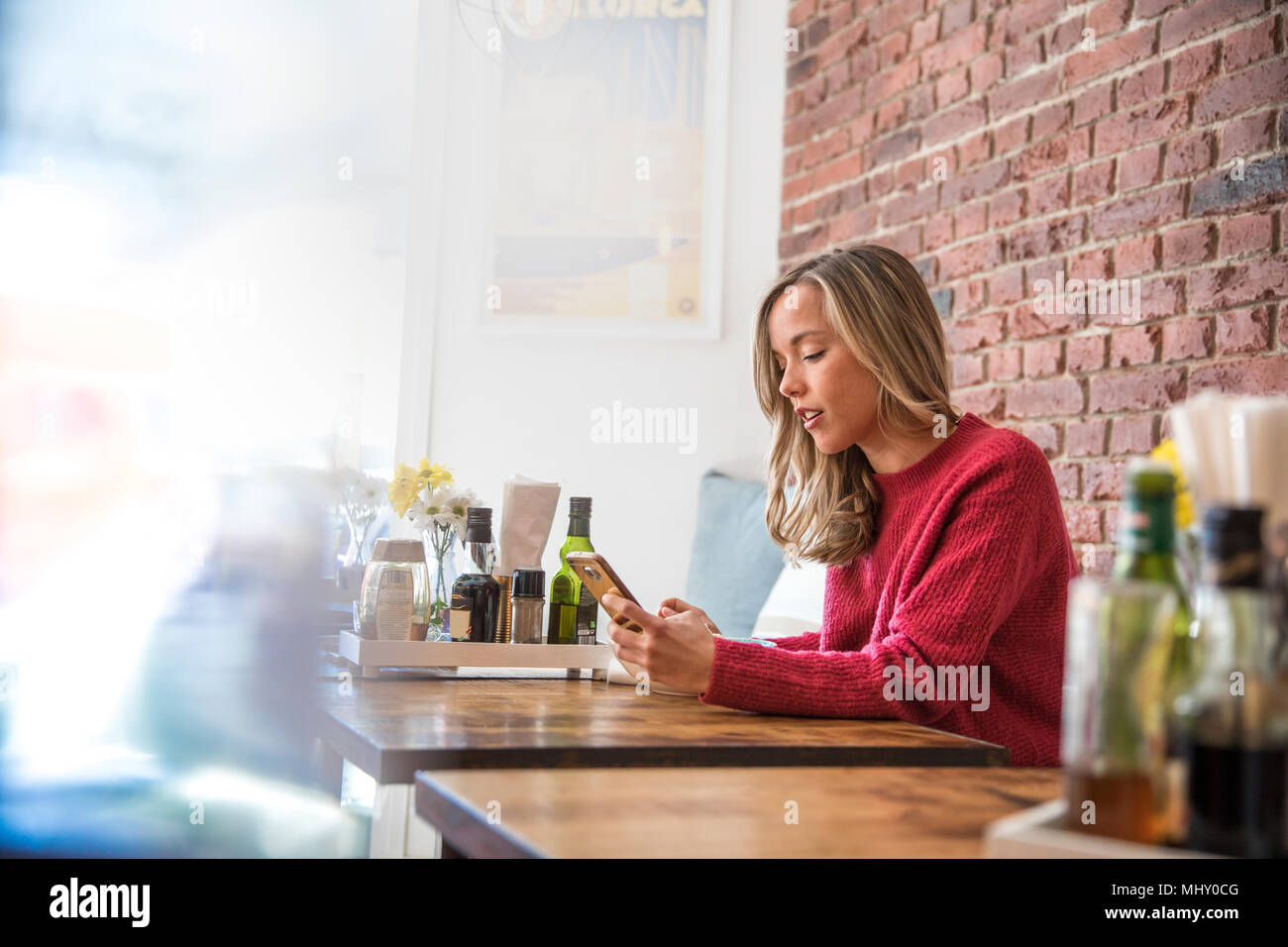 Woman sitting in cafe, looking at smartphone Photo Stock