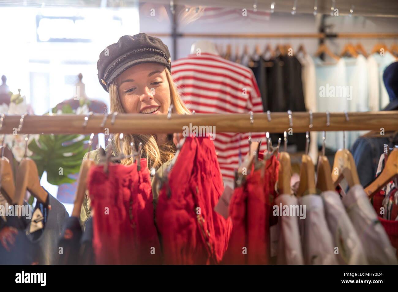Jeune femme shopping, à la recherche de vêtements sur rail en boutique Photo Stock