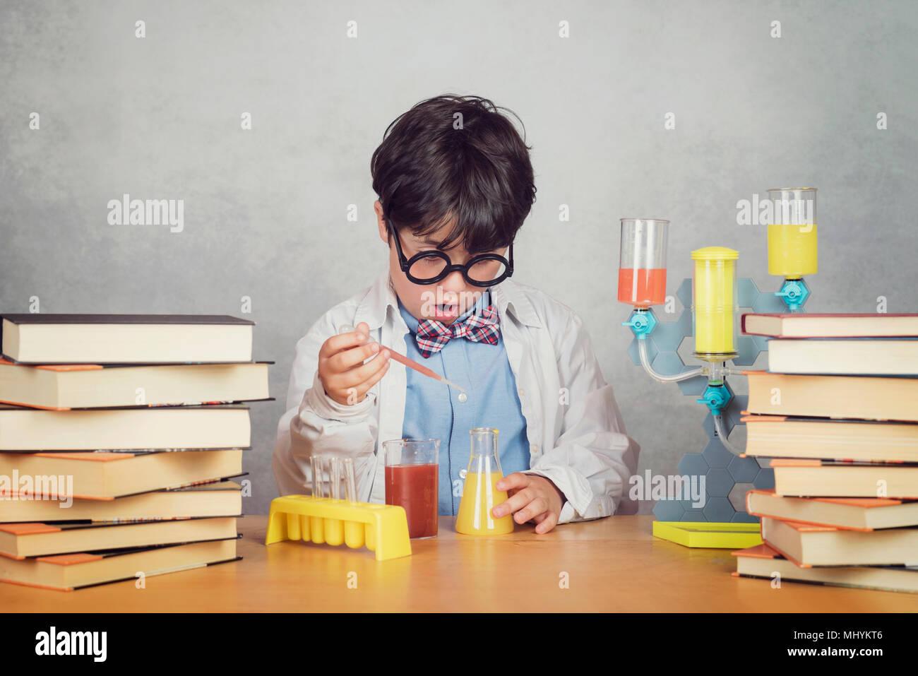 Garçon fait des expériences scientifiques dans un laboratoire sur fond gris Photo Stock
