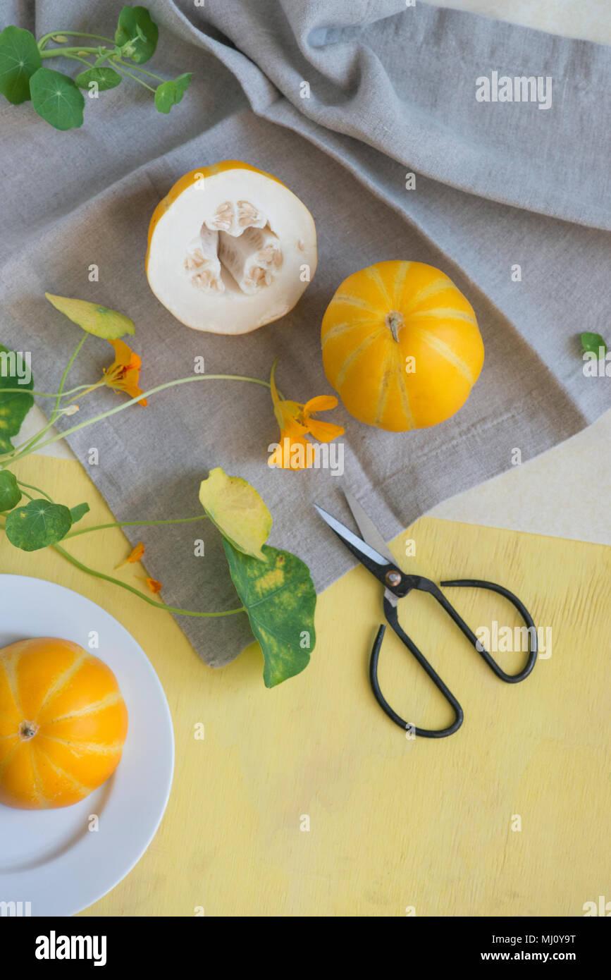 Nature morte au melon et de fleurs en jaune et gris. Photo Stock
