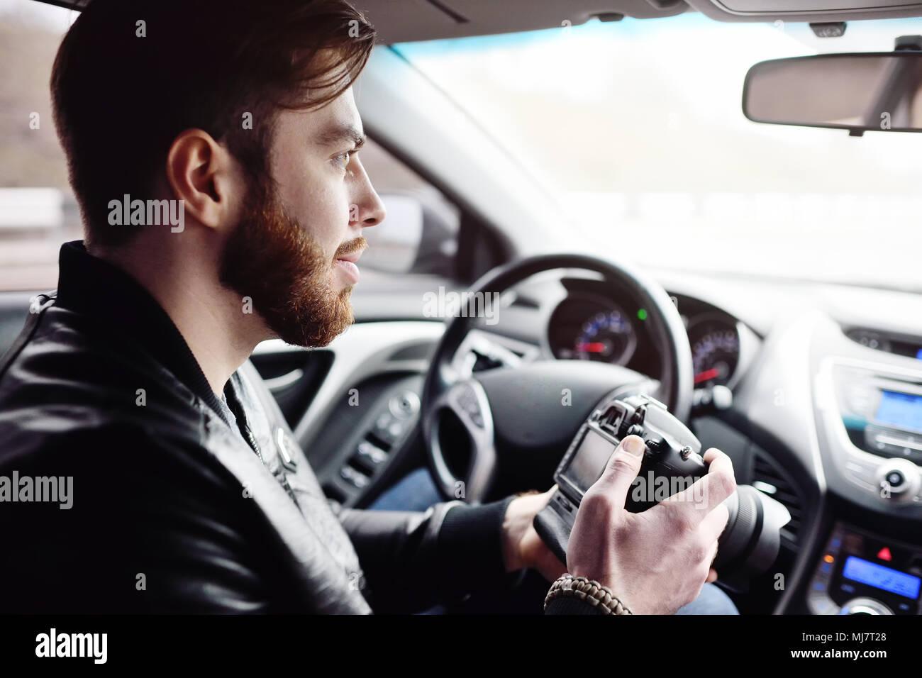 Jeune homme avec une caméra dans la voiture Photo Stock