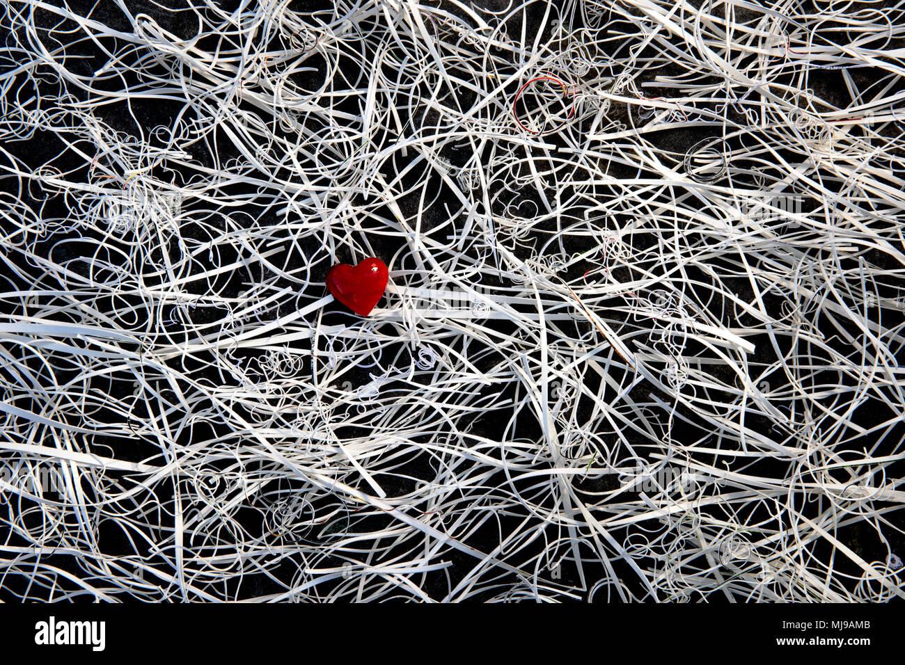 Un coeur en verre rouge au centre d'un enchevêtrement de restes de carte sur un fond d'ardoise. Photo Stock