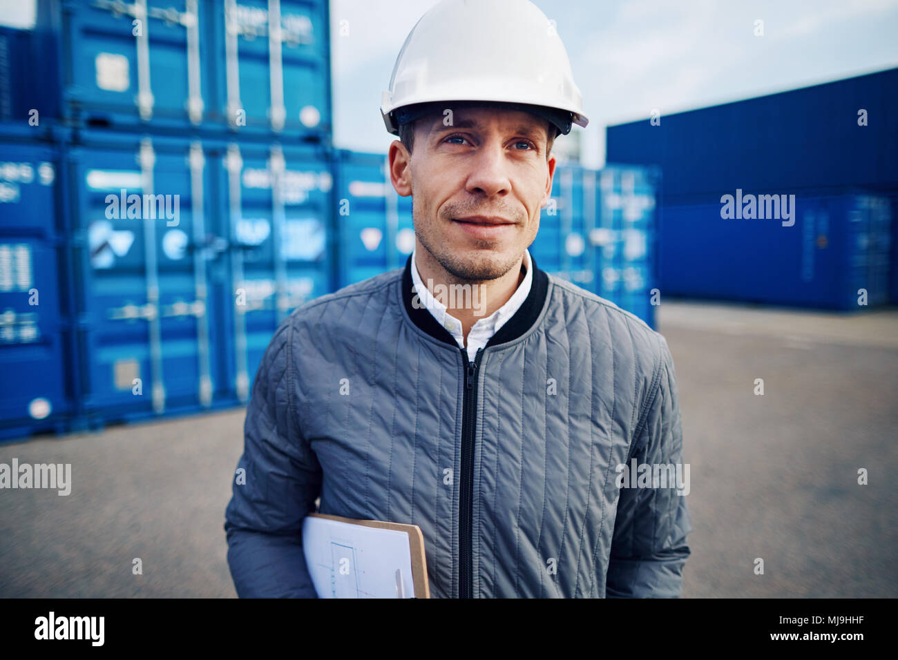 Gestionnaire de transport portant un casque de protection et souriant alors qu'il se trouvait seul sur une grande aire d'expédition commerciale détenant un presse-papiers Photo Stock